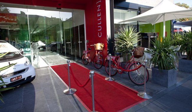 The exterior of the hotel. With bikes and cars available for guests to use.