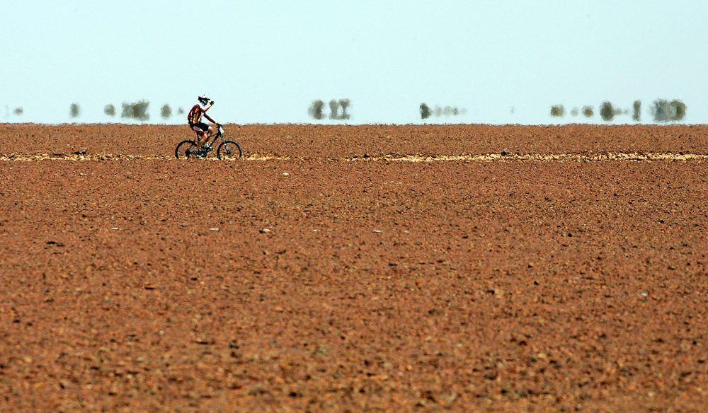 Mathew Dickerson from Dubbo, New South Wales takes a drink of water as he rides across a field of gibber rocks during day four of the Simpson Desert Bike Challenge.