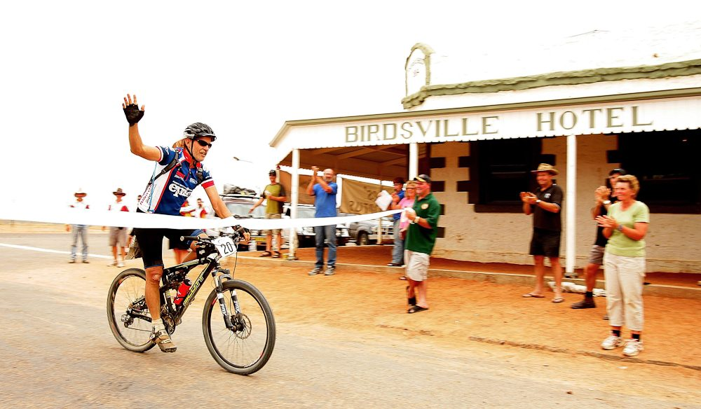 Bruce Wood waves to the crowd as he crosses the finish line in front of the legendary Birdsville Hotel on the final day of the Simpson Desert Bike Challenge race.