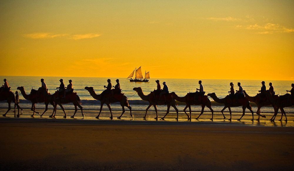 Beautifully restored and maintained pearling luggers trace their solemn and peaceful paths past Broome's iconic Cable Beach. Image by Tourism WA