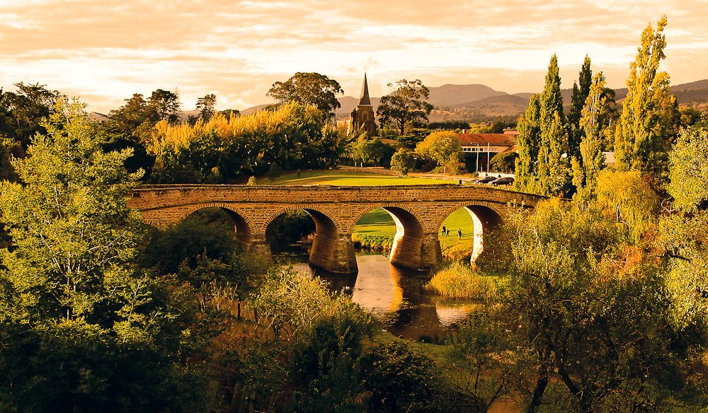 The ancient Richmond Bridge spans the Coal River, with Australia's oldest Catholic Church in the background. Image by Tourism Tasmania