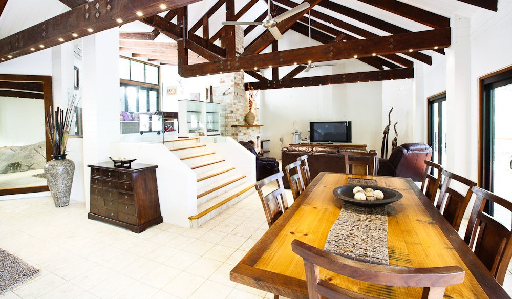 Living Area - Istania Holiday Home. High ceilings, plenty of natural light, plantation blinds, massive decorative boulders (inside and out!) and exposed beams.