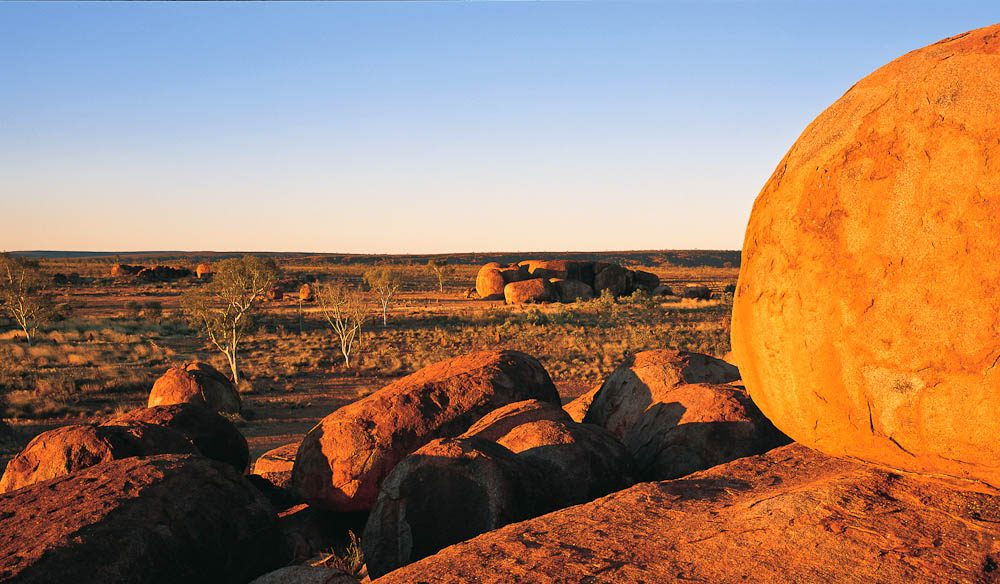 As a strange collection of boulders strewn across a spinifex valley in imposing, sometimes impossible positions, the Devils Marbles is unlike anything else. - Ken Duncan