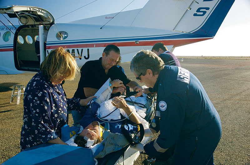 Dr Bill Hines prepares a patient for an emergency flight. Image by the RFDS