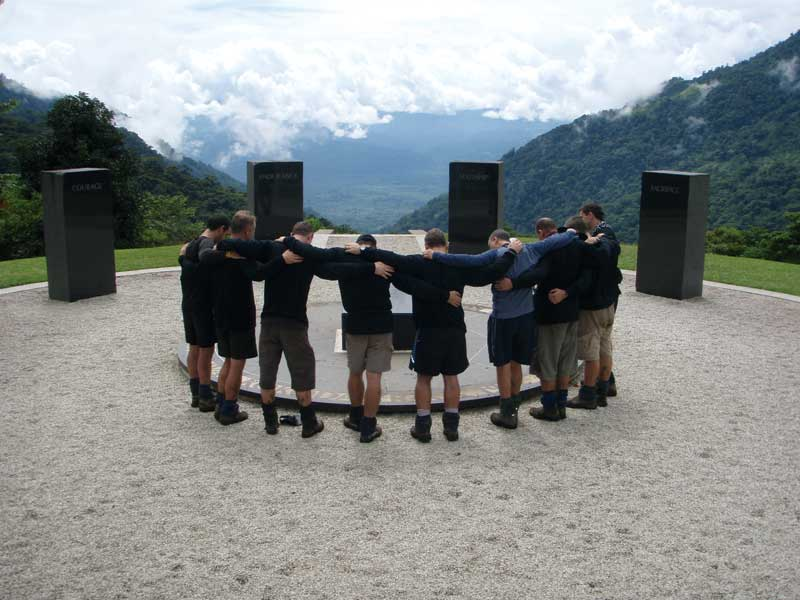 The four black granite pillars at Isurava along the Kokoda Trail are engraved with the words courage, endurance, mateship and sacrifice. Author Stu Lloyd is third from the right. Image by Tony Carr