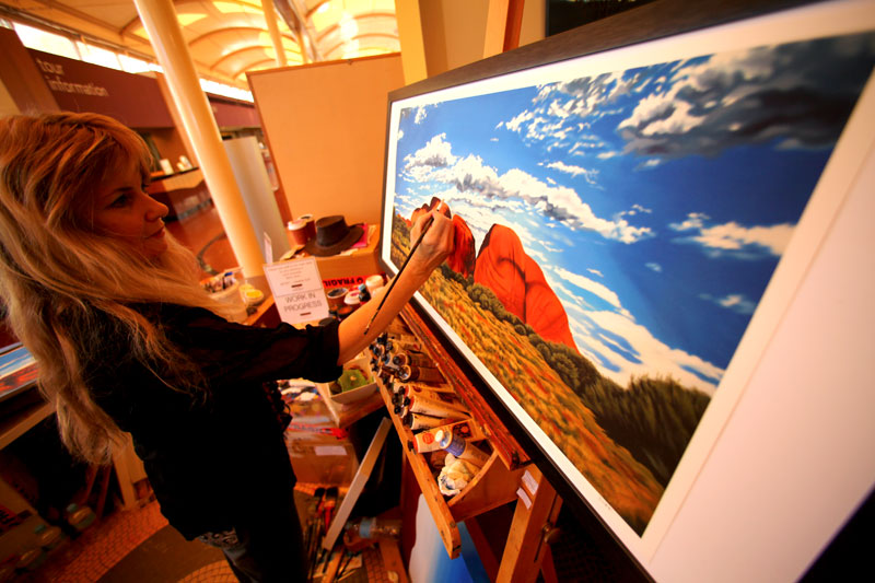 Artist Heather Duff at work as the artist in residence at Sails in the Desert at Uluru. Image by Greg Barton