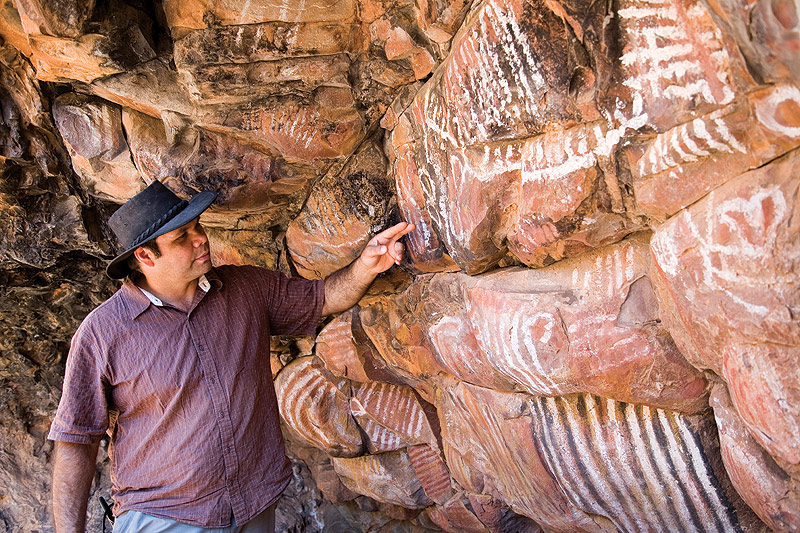 Haydyn shows off some of the ancient rock art. Image by Grenville Turner