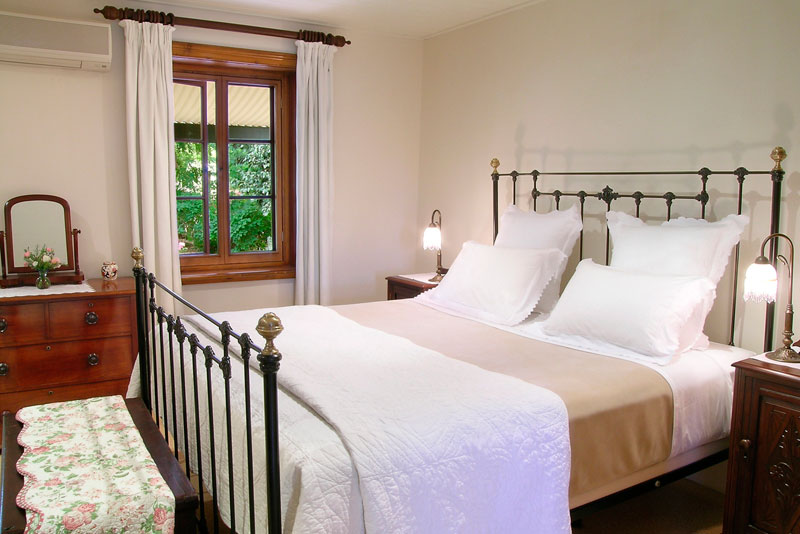 Huge iron bed, white bath robes, mini bar, gourmet dinner service (if desired), and bathroom with double French doors leading out on to the vineyard,