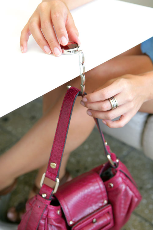 The Handbag Butler attaches to a tabletop to keep your bag above ground.
