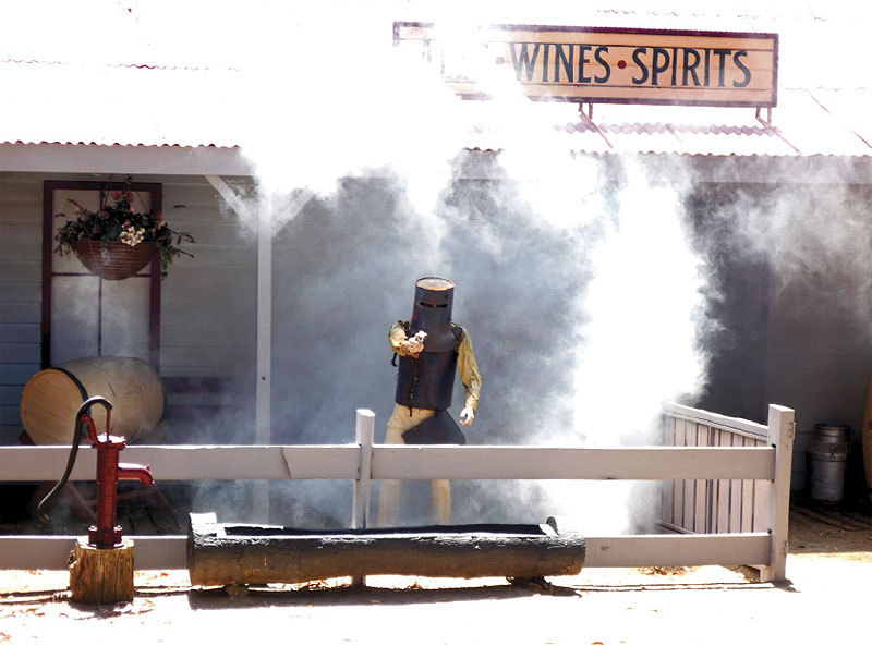 Ned blasts away as the Glenrowan Inn burns down around him.