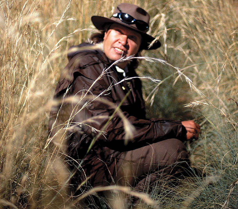 Uncle Doug Taylor, cross-cultural guide at the Desert Park, crouches in a sea of kangaroo grass.