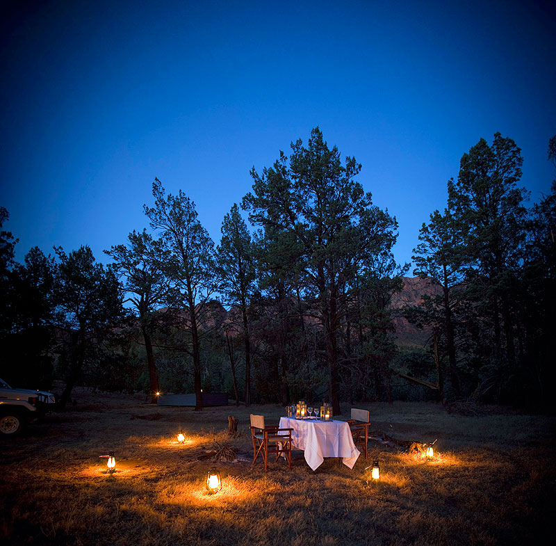 On a Walking Safari through Arkaba Station on the southern edge of SA's Flinders Ranges, gas lanterns surround a table set for two beneath a sky so clear a bug wouldn't dare wander by.