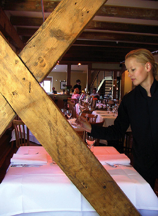 Waitress Bronwynn sets a table in the dining room.