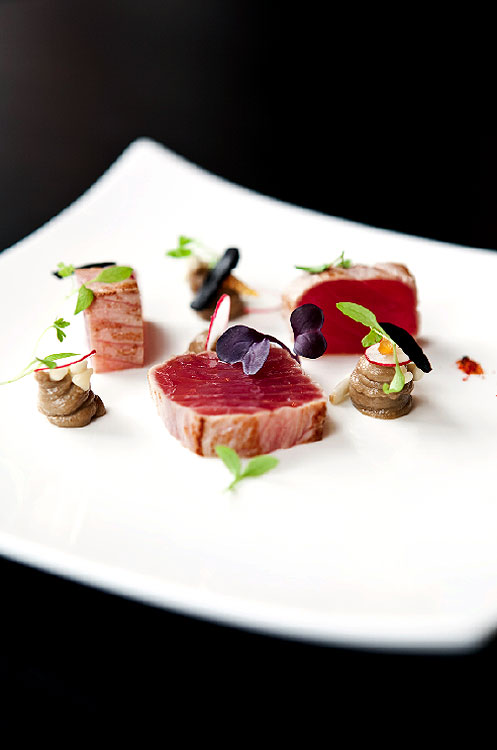 Seared yellow fin tuna, white radish, yuzu, enoki mushrooms, and black garlic.