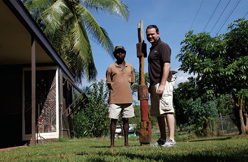 Quentin Long and Pedro Wonaeamirri pose with a  Jilamara Art Centre pukumani, or burial pole.