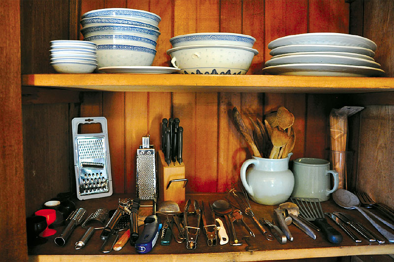 The homely kitchen's well-stocked utensil shelf.
