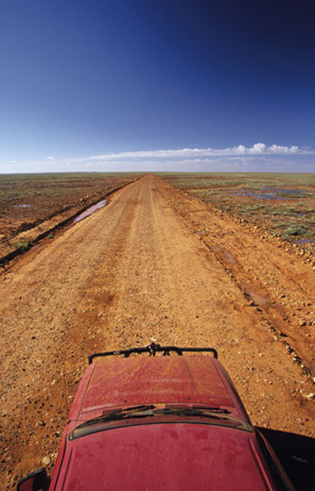 Driving through the flat expanse on the Old Ghan Heritage Trail. Image by Robyn Rosenfeldt