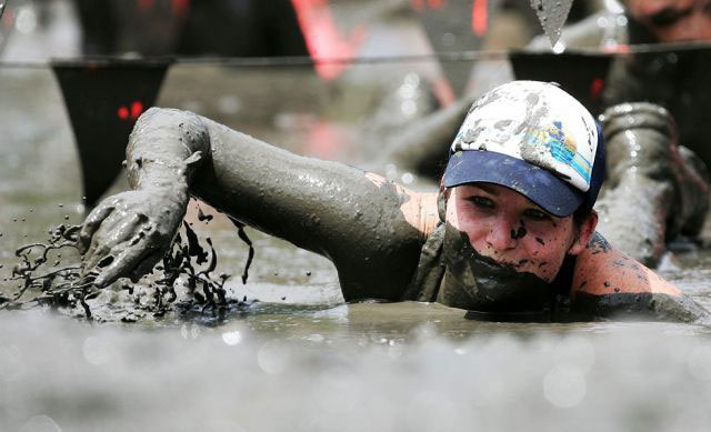 Compeitors run, slide and slither there way across the short or long courses at the Mud Race every December