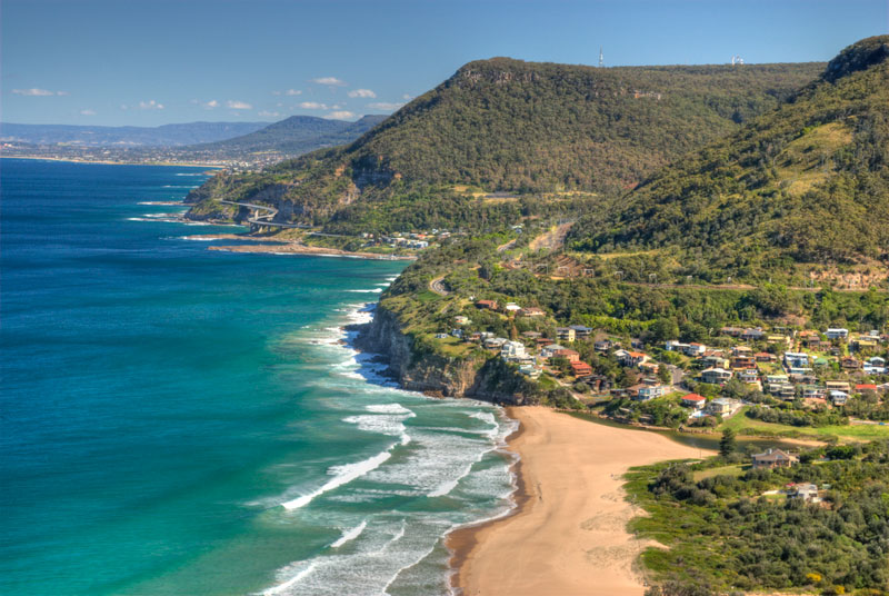This is a view of the Illawarra Coast south of Sydney from Stanwell Tops.  From here hang gliders take off for a landing on the beach at Stanwell Park below. The bridge snaking around the coast in the middle distance is Sea Cliff Bridge. Image by Ter