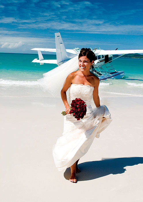 A bride alights from an Air Whitsundays plane on Whitehaven Beach; how's that for an entrance?