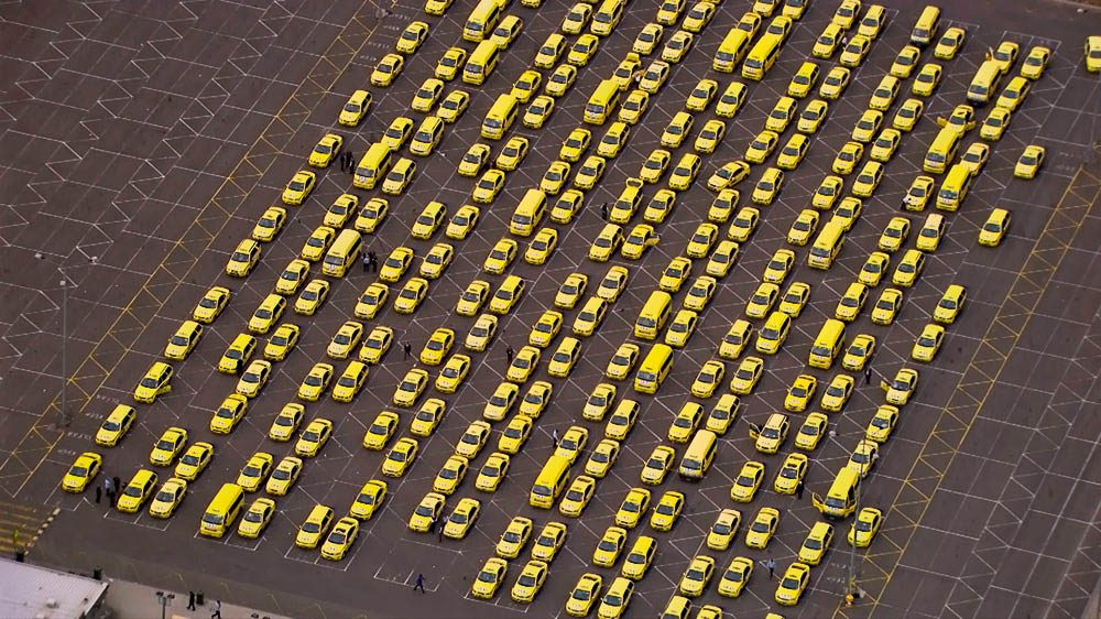 Yellow taxis wait patiently to join a queue for passengers at Melbourne airport, Victoria