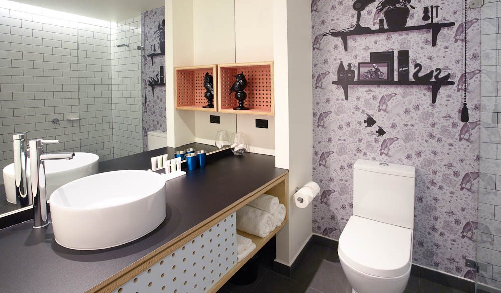 Atura's QT touches: Galah-and-Sturt-Desert-pea print wall paper with a 1970s vanity-top decal layered on top.