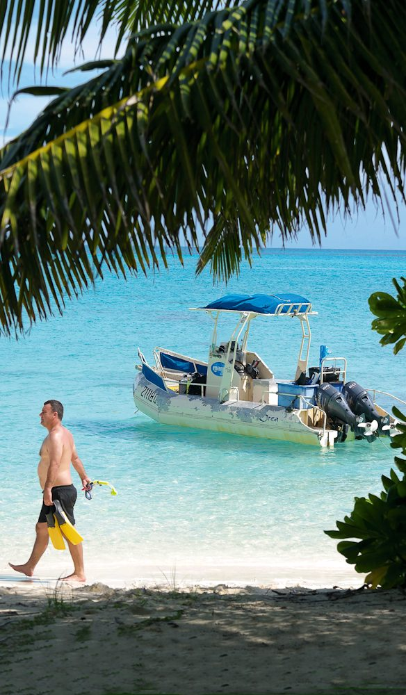 A lucky tourist strolls along Direction Island, Cocos Keeling.