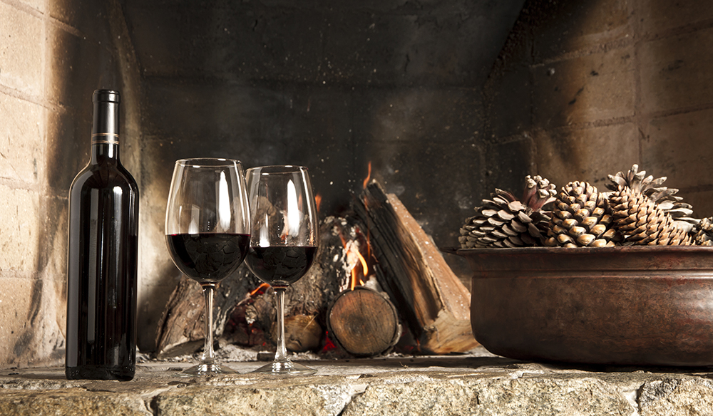 Romantic atmosphere. Bottle and wine glasses by the fireplace. Pine fruits.