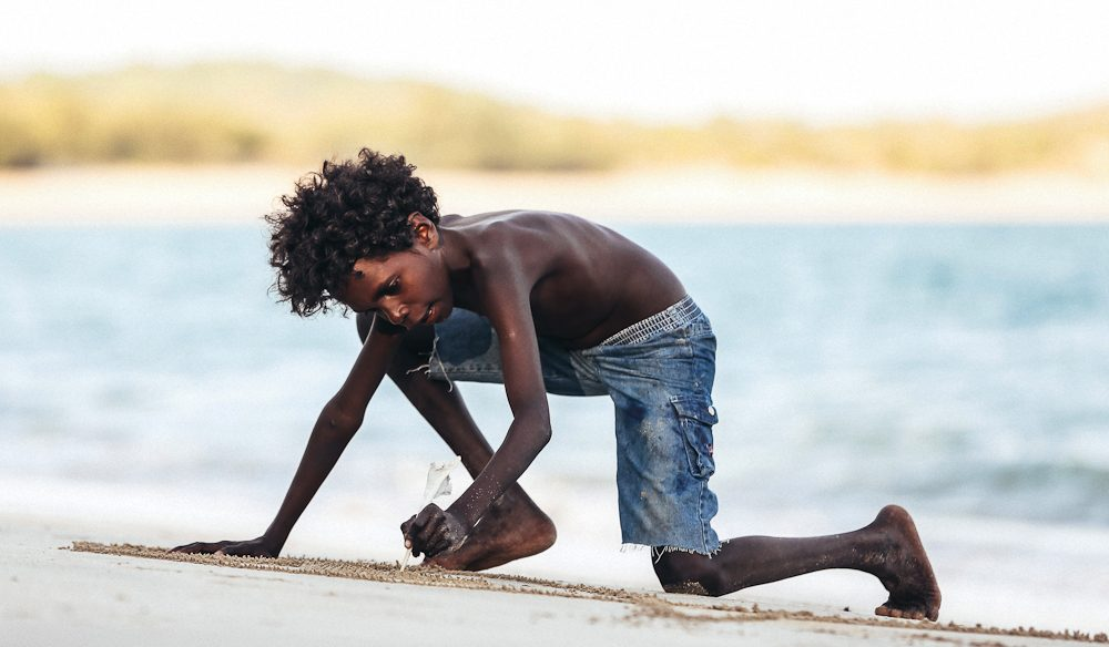 Tony Mununggurr draws turtles in the sand, Bukadal, East Arnhem Land (photo: Elise Hassey).