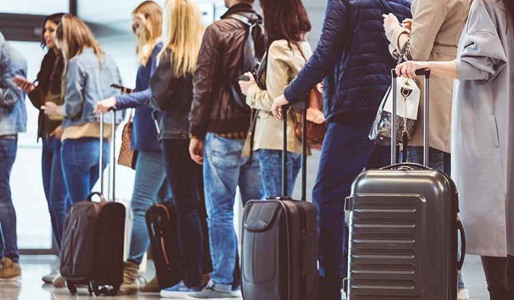 Group of people standing in queue to board airplane.