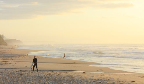 A Surfer walking along the golden expanse of Thirroul Beach in Wollongong (photo: Rachel Bartholomeusz).