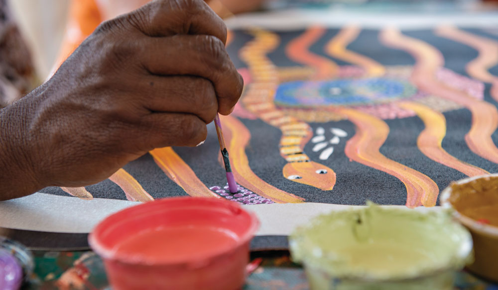 Artist at work; Maruku Arts Dot Painting Workshop in Yulara (photo: Tourism NT).