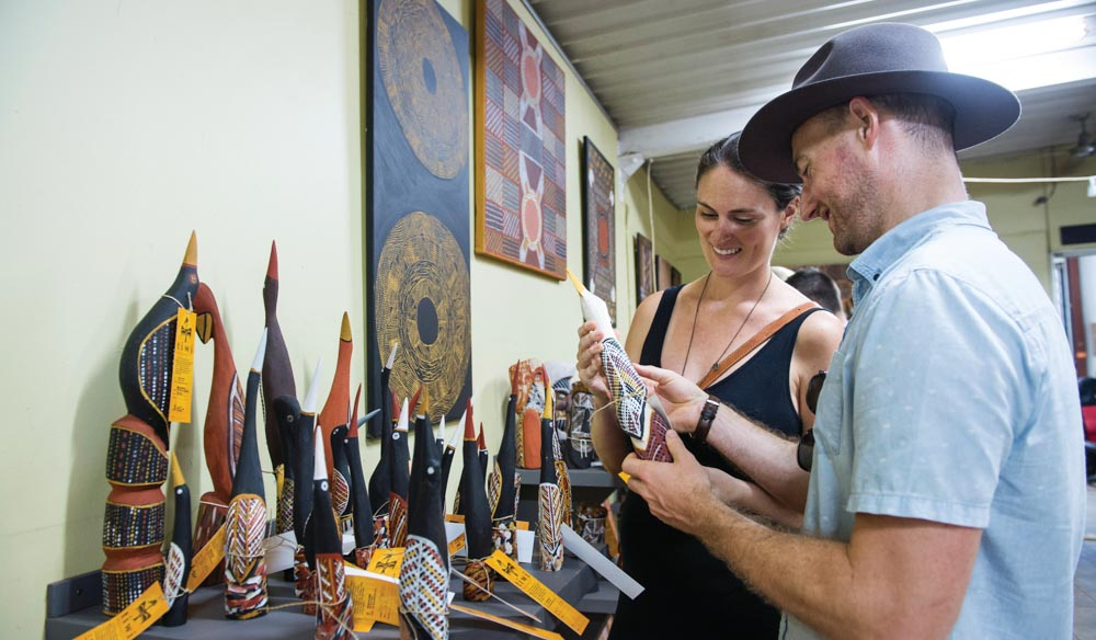 A couple shop for art at the Tiwi Islands Art Sale. The artwork is colourful and loaded with personality.