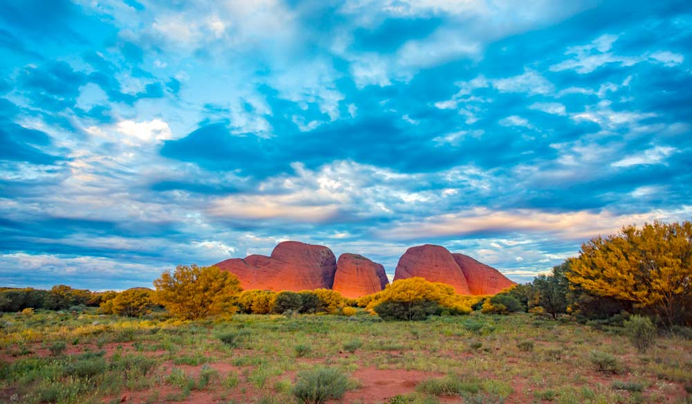 Another perspective of Uluru, set against a backdrop of dramatic clouds and blue skies. Kata Tjuta National Park.