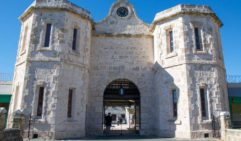 Old limestone architecture and arched entrance to the historic Fremantle Prison tourist attraction with tourists in Fremantle, Western Australia.