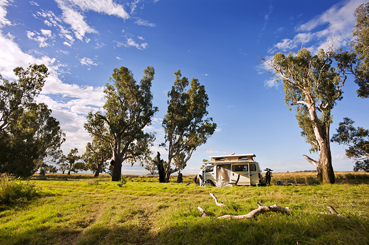 A motor home is set up, ready for camping in a quiet, secluded part of the Australian bush.