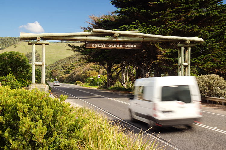 A campervan passes beneath the memorial arch on the Great Ocean Road in Victoria. The scenic road winds down the coast of Victoria and is popular with tourists.