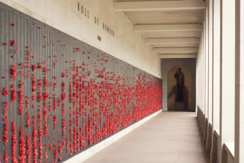 Poppies are placed beside names of deceased soldiers to honour them on the Wall of Remembrance at the Australian War Memorial in Canberra