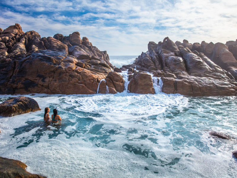 Girls swim in the natural rock pools at Injidup Beach in Yallingup.