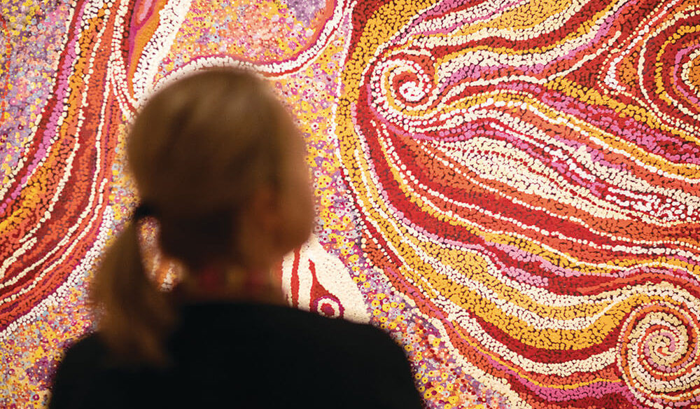 Woman looking at Aboriginal painting. Tourism NT and KWP!